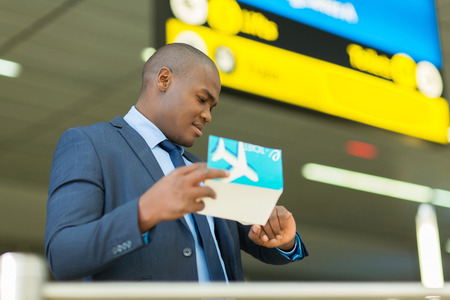 professional african american business traveller checking time at airport photo