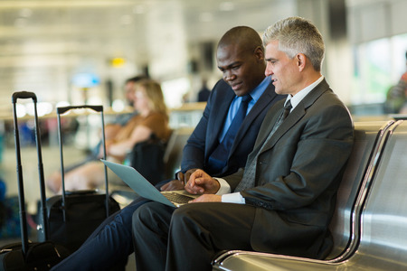 successful business travelers using laptop at airport photo