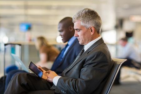 彼の飛行を待っている間タブレット コンピューターを使用して空港シニア男性旅客