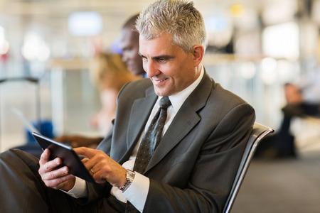 gente aeropuerto: Hombre de negocios mayor que usa el ordenador tableta mientras espera su vuelo en el aeropuerto Foto de archivo