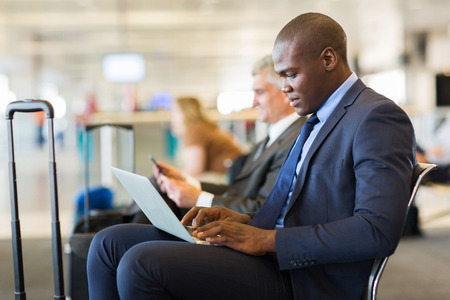 travel destination: young african american businessman using laptop while waiting for his flight