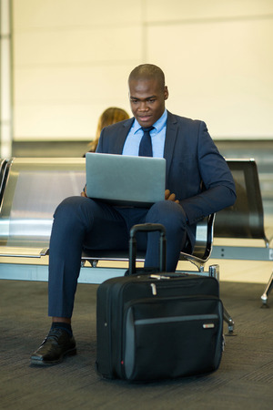 smart african businessman using tablet computer at airport photo