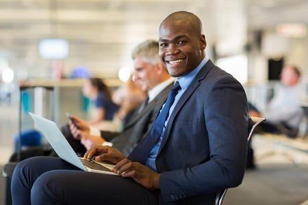Feliz viajero de negocios africano con el ordenador portátil en el aeropuerto Foto de archivo - 31969153