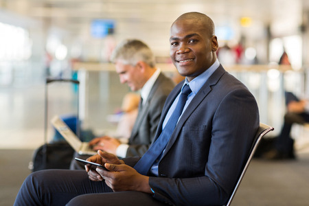 handsome african business traveller using tablet pc at airport photo