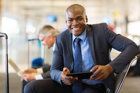 비행기를 기다리는 동안 태블릿 컴퓨터를 사용하여 공항에서 행복 한 아프리카 비즈니스 여행객