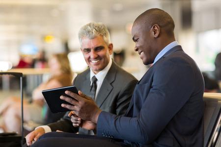 공항에서 태블릿 컴퓨터를 사용하는 명랑한 비즈니스 여행객