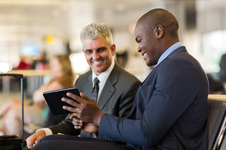 cheerful business travelers using tablet computer at airport