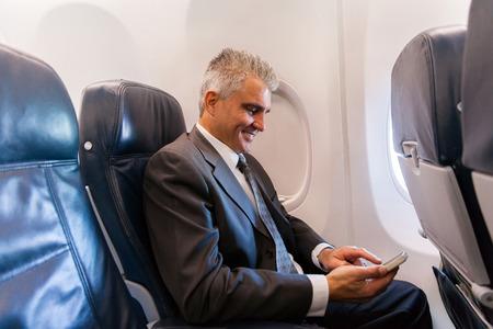 feliz hombre de negocios de mediana edad con teléfono celular en avión Foto de archivo