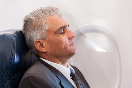peaceful senior businessman resting on airplane photo