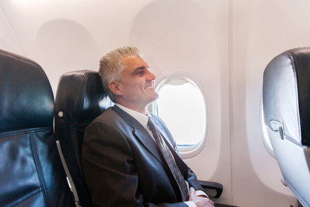 jetsetter: happy middle aged airplane passenger relaxing during flight on air plane