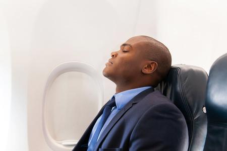 cabaña: apuesto hombre de negocios africano descansando en avión