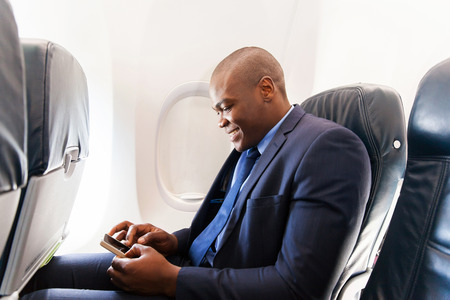 traveller: happy african airplane passenger using smart phone on plane Stock Photo