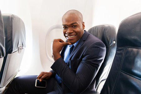 american airlines: young african american businessman holding cell phone on airplane Stock Photo