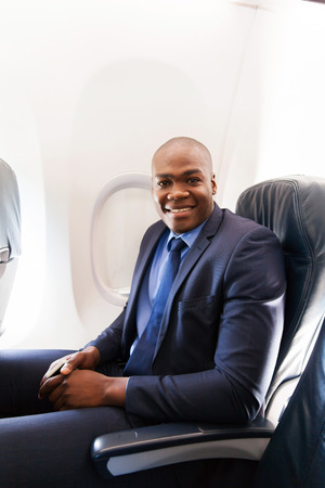 jetsetter: portrait of young african american businessman on airplane