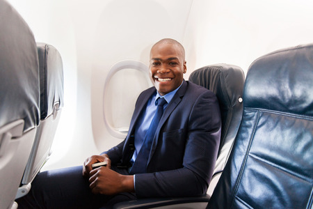 american airlines: cheerful afro american businessman on board of an airplane during the flight Stock Photo
