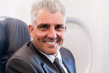 jetsetter: portrait of smiling senior businessman on airplane Stock Photo