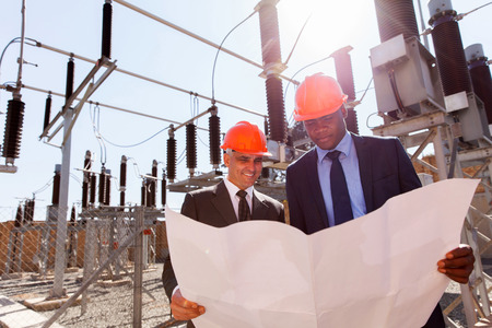 electricity substation: power company managers discussing blueprint at electrical substation