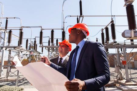 ingenieria el�ctrica: gerentes industriales que trabajan en la subestaci�n el�ctrica Foto de archivo