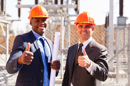 man thumbs up: portrait of electrical inspectors giving thumbs up at substation
