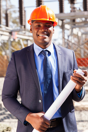 electricity substation: handsome african power company manager standing in electrical substation