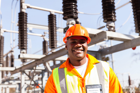 electricity substation: portrait of smiling african electrical engineer  Stock Photo
