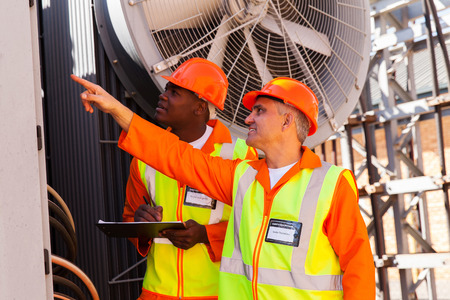 electricity substation: senior technician and young electrician working together in power plant Stock Photo