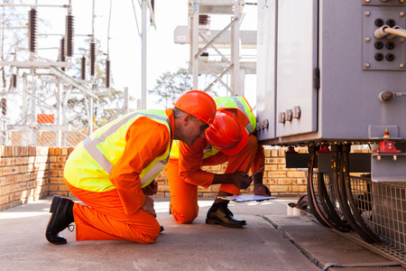 engineering clipboard: experienced electrical engineers working in substation Stock Photo