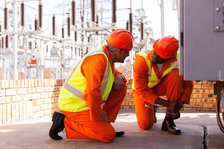 twee ervaren elektriciens bespreken van het werk in elektrische onderstation Stockfoto