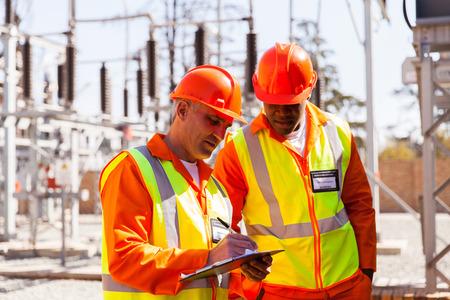 obreros: t�cnico superior profesional e ingeniero el�ctrico escrito en el portapapeles en la subestaci�n