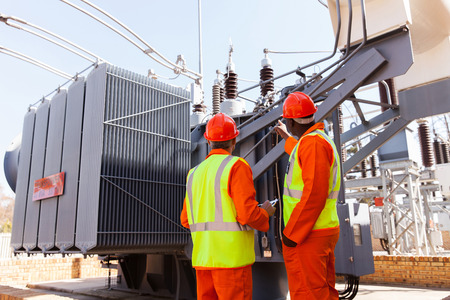 electricidad industrial: vista posterior de los electricistas de pie junto a un transformador en la planta de energía eléctrica