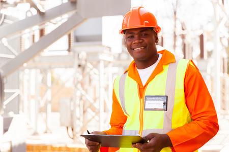 knappe mannelijke Afrikaanse elektrisch ingenieur in onderstation Stockfoto