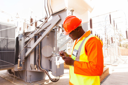 workplace safety: handsome afro american electrical engineer writing on clipboard in power plant