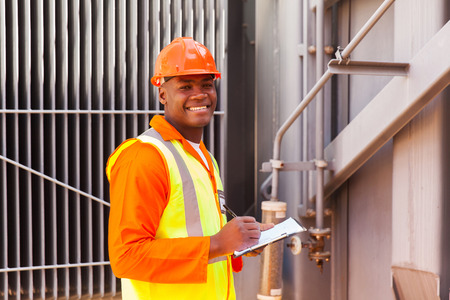 electricity substation: male african electrical worker in front of transformer Stock Photo