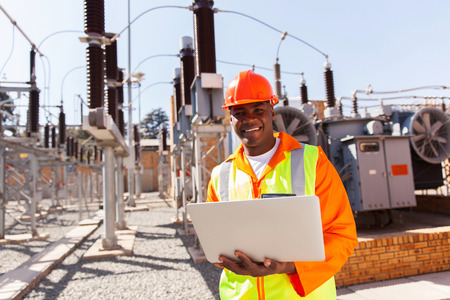 professional african electrical engineer using laptop computer in substation Foto de archivo