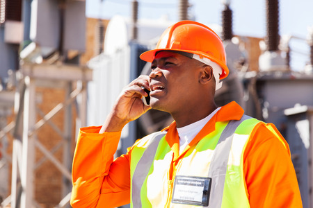 ingenieria el�ctrica: ingeniero el�ctrico africano usando el tel�fono celular en la subestaci�n Foto de archivo