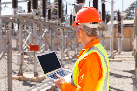 electricity substation: senior technician holding laptop computer in substation Stock Photo