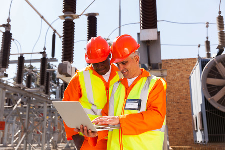 two modern electrical technicians using laptop in substation photo