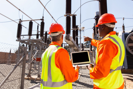 industrial worker: rear view of electricians with laptop pointing in substation