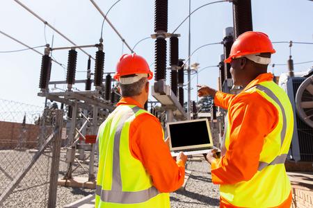energia electrica: vista posterior de los electricistas con el ordenador port�til que apunta en la subestaci�n