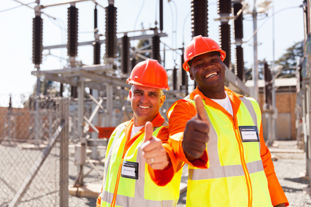 electricity substation: two cheerful technicians giving thumbs up in substation Stock Photo