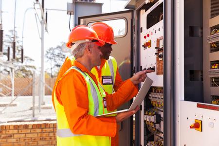 electricista: ingenieros el�ctricos profesionales de ajuste ajustes del transformador Foto de archivo