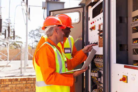 electricity substation: professional electrical engineers adjusting transformer settings