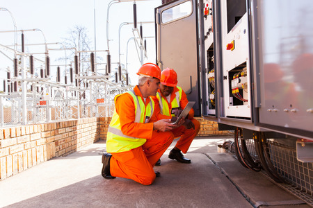 electricista: dos ingenieros eléctricos que discuten el trabajo en la subestación Foto de archivo