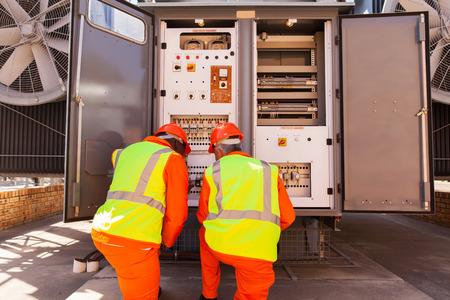ingeniero electrico: electricistas masculinos reparación de transformador en la subestación