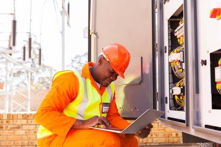 tablero de control: apuesto ingeniero eléctrico africano que trabaja en la computadora portátil junto al transformador