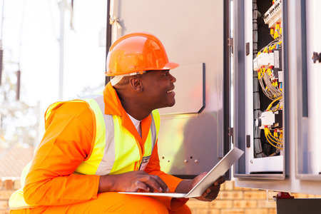 experienced african electrician checking computerized machine status with laptop Stock Photo