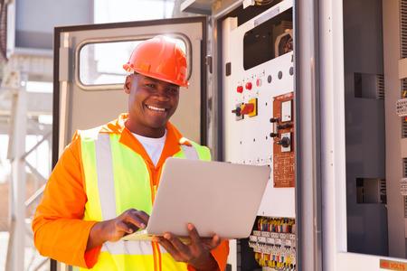 ingeniero electrico: Retrato de feliz joven ingeniero eléctrico africano con el ordenador portátil Foto de archivo
