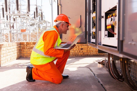 electricity substation: successful mid age electrician kneeing in front of transformer