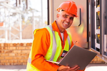 electrical panel: happy middle aged electrical engineer using laptop next to transformer Stock Photo