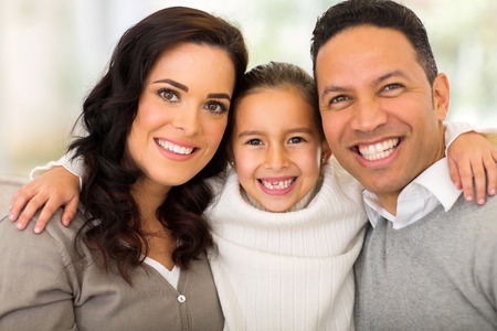 middle aged woman smiling: portrait of pretty little girl hugging her parents at home Stock Photo